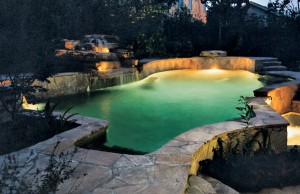 inground pool at night with LED lighting and a cascade waterfall