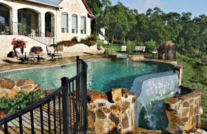 infinity edge free form pool with spa with spillover and flagstone deck