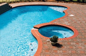 free form pool with built-in benches with tile details and a spa