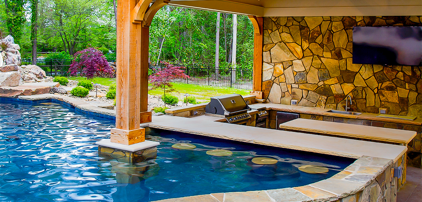 custom pool with swim up bar and outdoor kitchen