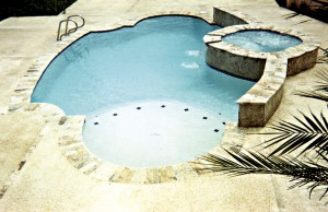 Geometric swimming pool with tanning ledge and spa