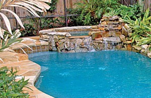 Gunite spa with cascade edge and rock waterfall