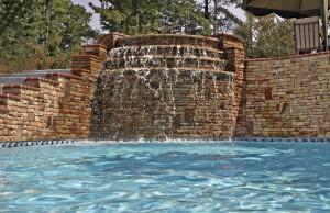 Raised gunite spa with rock waterfall steps