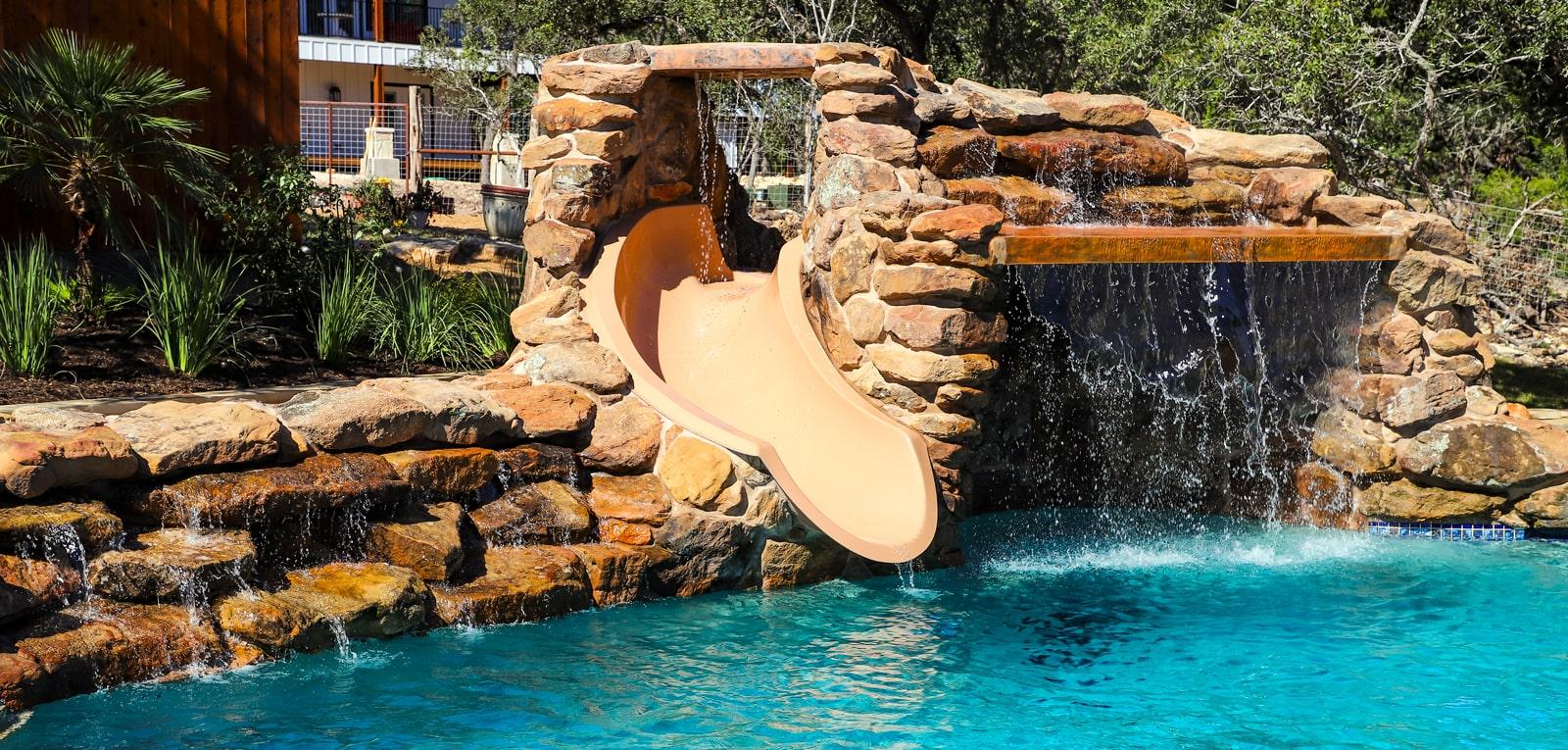 inground pool with rock waterfall slide