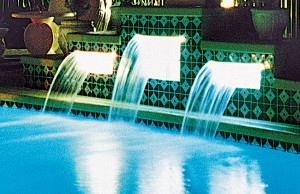Swimming pool with lit cascade waterfalls