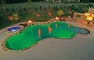 Swimming pool and spa with color changing lights showing green and blue