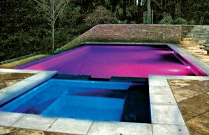 Swimming pool and spa with color changing lights showing blue and purple