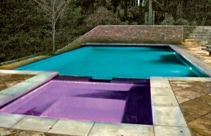Swimming pool and spa with color changing lights showing purple and blue