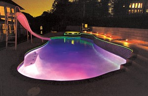 Swimming pool with color changing lights showing purple