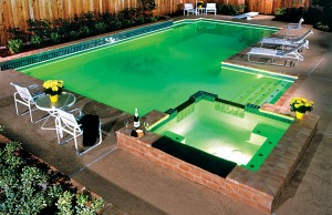 Swimming pool and spa showing with color changing lights showing green