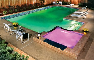 Swimming pool and spa showing with color changing lights showing green and pink