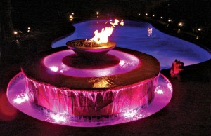 Swimming pool and fountain with color changing lights showing pink