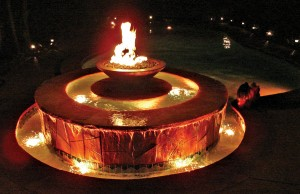 Swimming pool and fountain with color changing lights showing orange