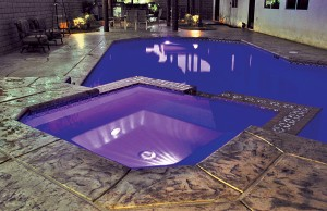Swimming pool and spa with color changing lights showing purple