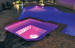 Swimming pool and spa with color changing lights showing pink