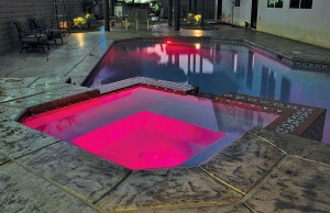Swimming pool and spa with color changing lights showing red