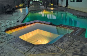 Swimming pool and spa with color changing lights showing orange
