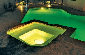 Swimming pool and spa with color changing lights showing yellow