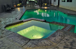 Swimming pool and spa with color changing lights showing green