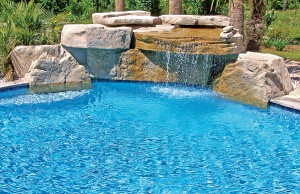 Swimming pool with large rock waterfall