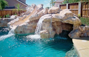 Swimming pool with rock waterfall grotto and slide