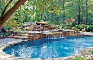 Rock waterfall flowing into swimming pool