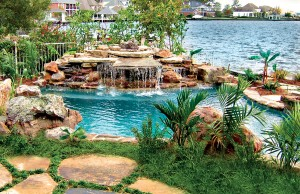 Rock waterfall and swimming pool next to lake