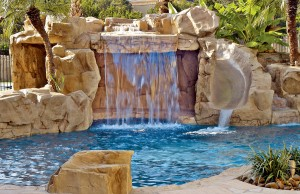 Swimming pool with rock waterfall grotto and water slide