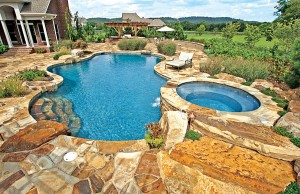 Free form swimming pool with spa and rock steps
