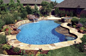 Free form swimming pool with tanning ledge and rock waterfall