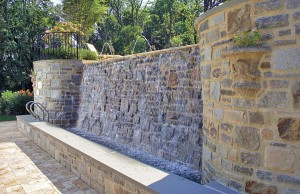 Raised vanishing edge pool with rock waterfall and laminar jets