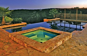 vanishing edge pool with spa at night