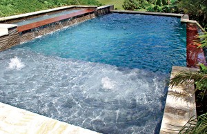 infinity edge pool with cascade waterfall and tanning ledge